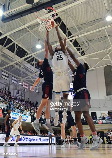 Mikal Bridges of the Villanova Wildcats puts up a shot between Ryan Betley and Jarrod Simmons of the Pennsylvania Quakers at Jake Nevin Field House...