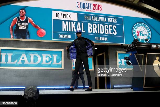 Mikal Bridges walks the stage after being selected tenth overall by the Philadelphia 76ers on June 21 2018 at Barclays Center during the 2018 NBA...