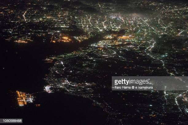 Mikawa Bay, Chubu Centrair International Airport (NGO) and Nagoya city in Japan night time aerial view from airplane