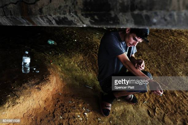 Mike a heroin addict who began using opiates when he was 13 pauses to shootup by a railway underpass in the Kensington section of Philadelphia which...