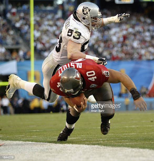 Mike Alstott of the Tampa Bay Buccaneers carries the ball as he is pushed out of bounds by an airborne Bill Romanowski of the Oakland Raiders during...