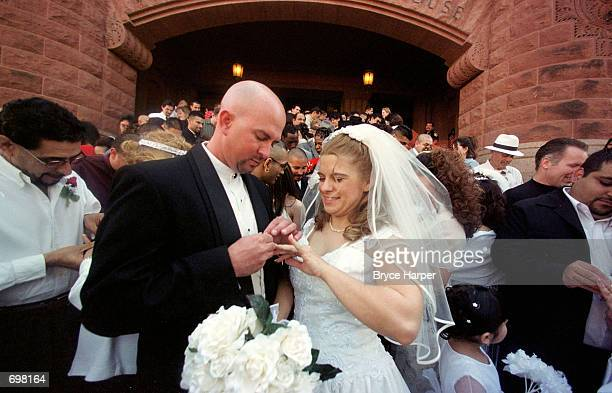Mike and Shelly Bell exchange rings during in a mass wedding February 14 2002 on the steps of Bexar County Courthouse in San Antonio TX The...