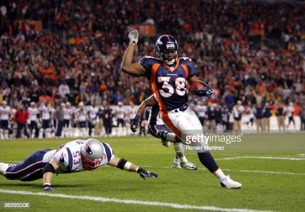 Mike Anderson of the Denver Broncos runs for his second touchdown past Larry Izzo of the New England Patriots during the AFC Divisional Playoff game...