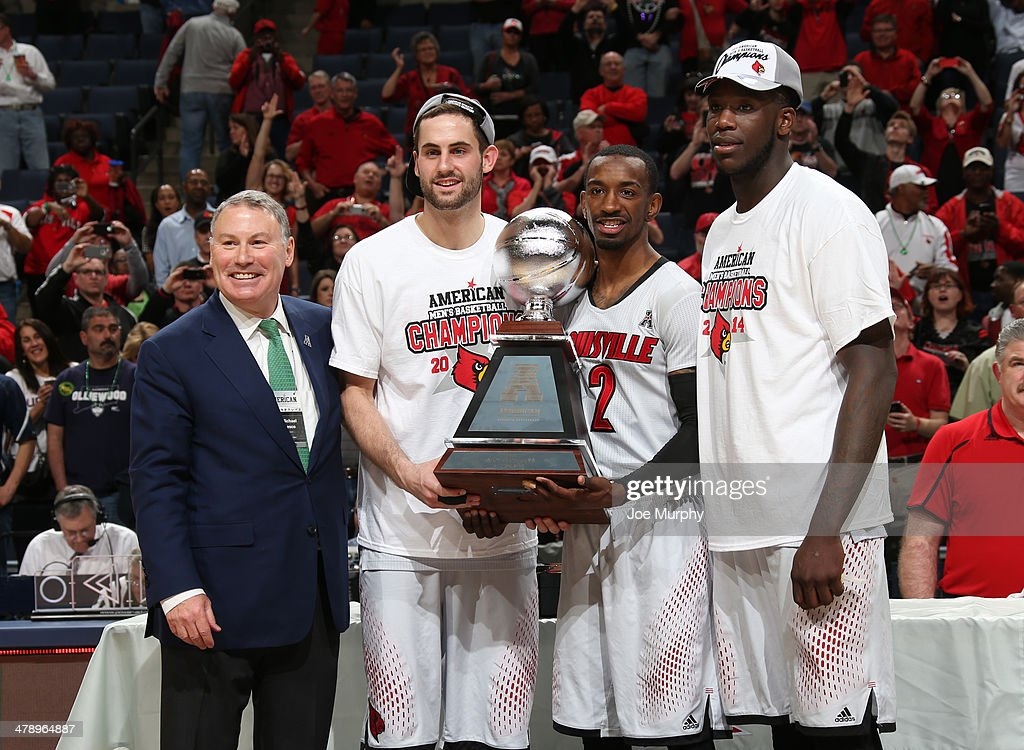 Mike Aresco, Commisioner of the AAC poses with Luke Hancock #11, Russ Smith #2 and Montrezl Harrell #24 of The Louisville Cardinals after presenting the championship trophy against the Connecticut Huskies during the Championship of the American Athletic Conference Tournament at FedExForum on March 15, 2014 in Memphis, Tennessee. Louisville defeated Connecticut 71-61.