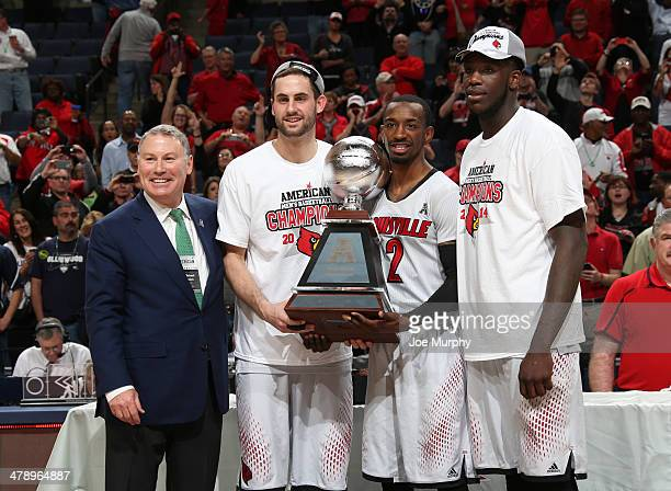 Mike Aresco Commisioner of the AAC poses with Luke Hancock Russ Smith and Montrezl Harrell of The Louisville Cardinals after presenting the...