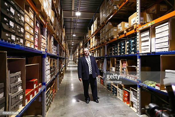 Mike Ashley billionaire and founder of Sports Direct International Plc poses for a photograph in an aisle at his company's warehouse following the...