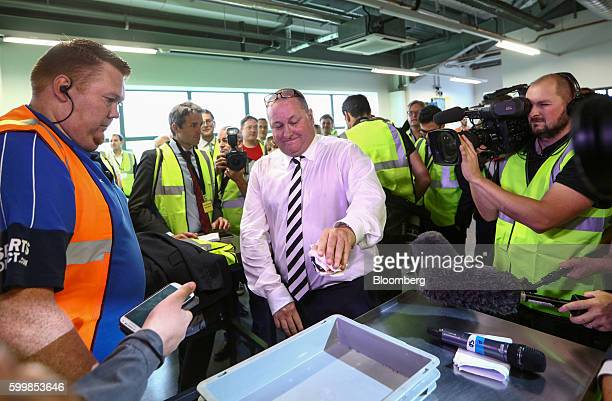 Mike Ashley billionaire and founder of Sports Direct International Plc places his wallet and a wad of 50 pound banknotes as he demonstrates the...