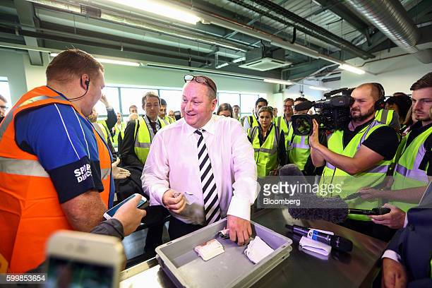 Mike Ashley billionaire and founder of Sports Direct International Plc retrieves his wallet and a wad of 50 pound banknotes from a tray as he...