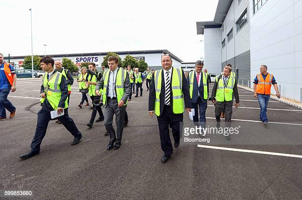 Mike Ashley billionaire and founder of Sports Direct International Plc center walks with attendees during a tour of the company's warehouse following...