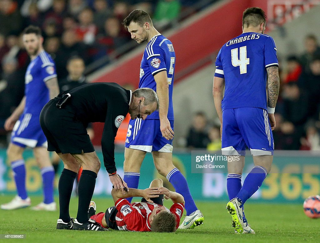 Mike Atkinson the referee atends to Lloyd Isgrove of Southampton who had suffered a head injury during the FA Cup Third Round match between Southampton and Ipswich Town at St Mary's Stadium on January 4, 2015 in Southampton, England.