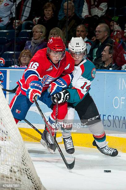 Mike Aviani of the Spokane Chiefs checks Rourke Chartier of the Kelowna Rockets during the first period on March 5, 2014 at Prospera Place in...