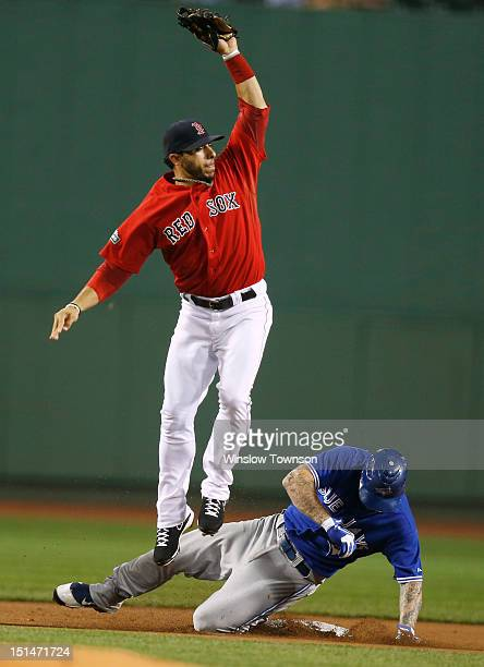 Mike Aviles of the Boston Red Sox goes high to get a throw as Brett Lawrie of the Toronto Blue Jays slides in safely with a double during the first...
