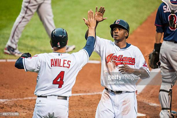 Mike Aviles of the Cleveland Indians and Nyjer Morgan celebrate after both scoring on a hit by Michael Brantley during the third inning against the...
