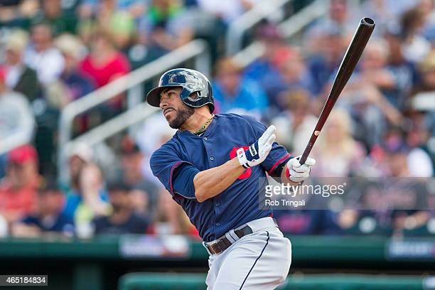 Mike Aviles of the Cleveland Indians singles in the fourth inning during a spring training game against the Cincinnati Reds at Goodyear Ballpark on...