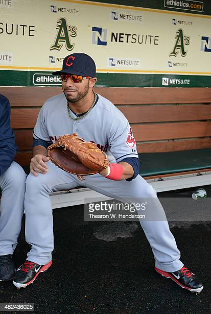 Mike Aviles of the Cleveland Indians sits in the dugout with a catchers glove on prior to the start of his game against the Oakland Athletics at Oco...