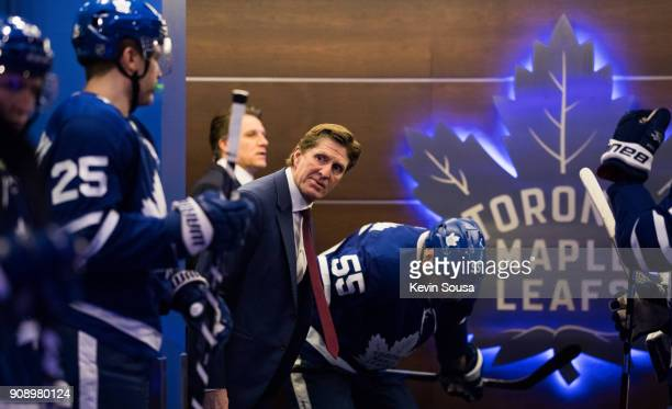 Mike Babcock of the Toronto Maple Leafs looks out of the dressing room as the Leafs wait to take the ice for the second period of play against the...
