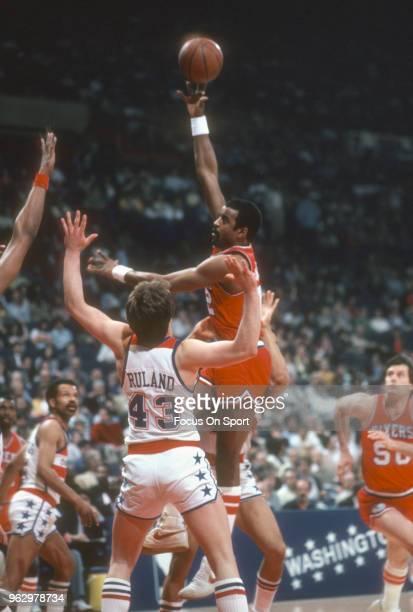 Mike Bantom of the Philadelphia 76ers shoots over Jeff Ruland of the Washington Bullets during an NBA basketball game circa 1982 at the Capital...