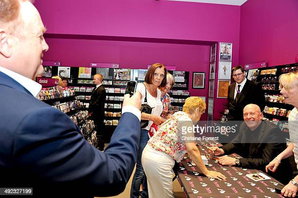 Mike Batt takes a camera phone picture of Bob Blakeley signing copies of his debut album 'Performance' at HMV Manchester on May 19 2014 in Manchester...