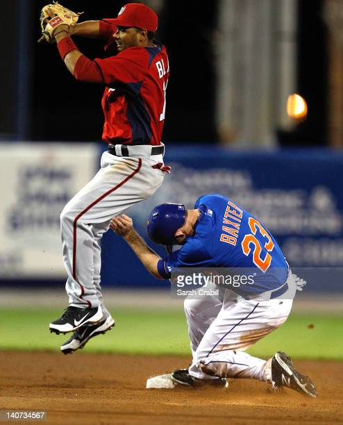 Mike Baxter of the New York Mets steals second base under Andres Blanco of the Washington Nationals during a preseason game at Digital Domain Park on...