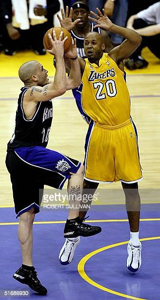 Mike Bibby of the Sacramento Kings goes up for a shot as Brian Shaw of the Los Angeles Lakers guards him during 2nd quarter action of Game 4 of the...