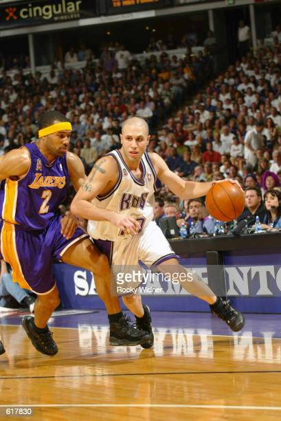 Mike Bibby of the Sacramento Kings looks to drive the ball past Derek Fisher of the Los Angeles Lakers during Game 7 of the 2002 NBA Western...
