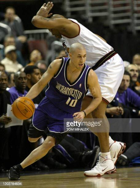 Mike Bibby of the Sacramento Kings runs around Derrick Coleman of the Philadelphia 76ers as he heads to the basket in the 1st period of their game 06...