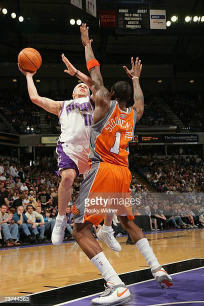 Mike Bibby of the Sacramento Kings takes the ball to the basket against Amare Stoudemire of the Phoenix Suns during the game at Arco Arena on March...