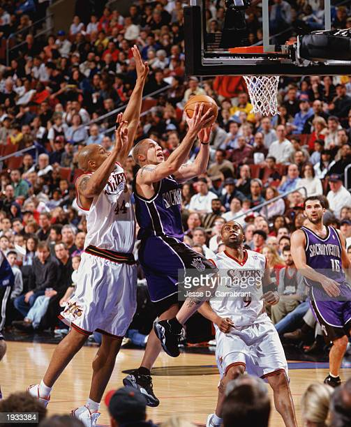 Mike Bibby of the Sacramento Kings takes the ball up against Derrick Coleman of the Philadelphia 76ers during the game at First Union Center on April...