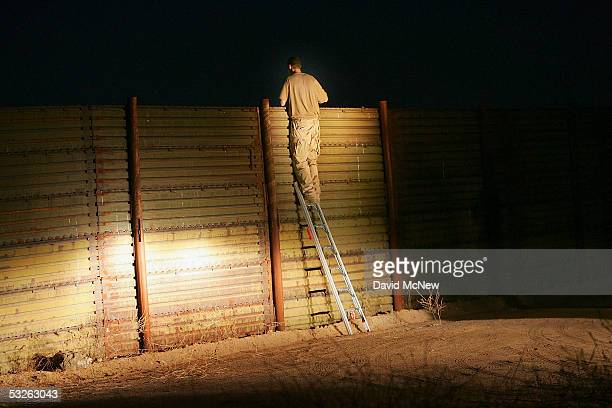 Mike 'Big Bird' Bird takes a look over the USMexico border fence during the nightly patrol by citizen volunteers searching for people crossing into...