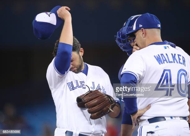 Mike Bolsinger of the Toronto Blue Jays is visited on the mound by pitching coach Pete Walker in the fifth inning during MLB game action against the...