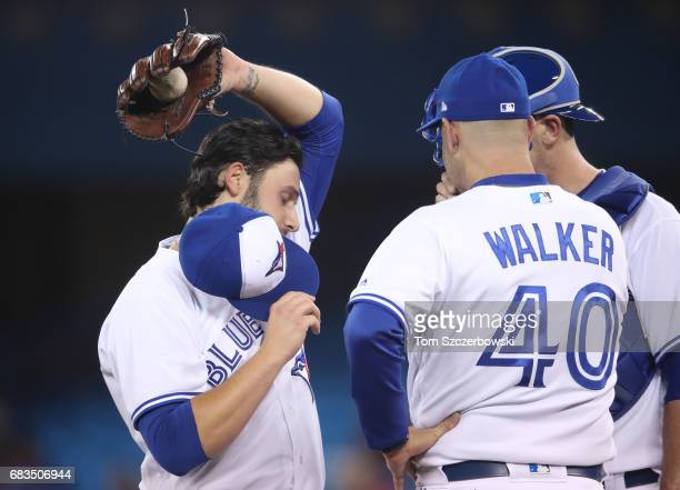 Mike Bolsinger of the Toronto Blue Jays reacts as he is visited on the mound by pitching coach Pete Walker in the fifth inning during MLB game action...