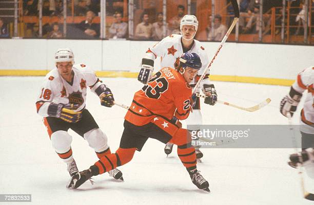 Mike Bossy of the Campbell Conference and New York Islanders skates on the ice as Marcel Dionne of the Wales Conference and Los Angeles Kings and...