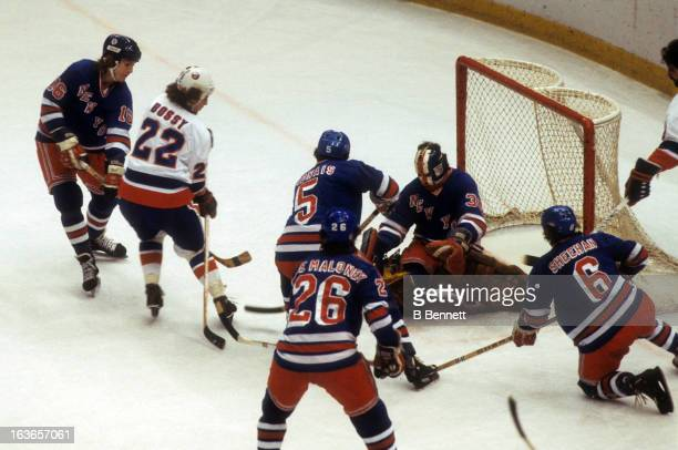 Mike Bossy of the New York Islanders goes for the puck against goalie John Davidson Pat Hickey Carol Vadnais Dave Maloney and Bobby Sheehan of the...