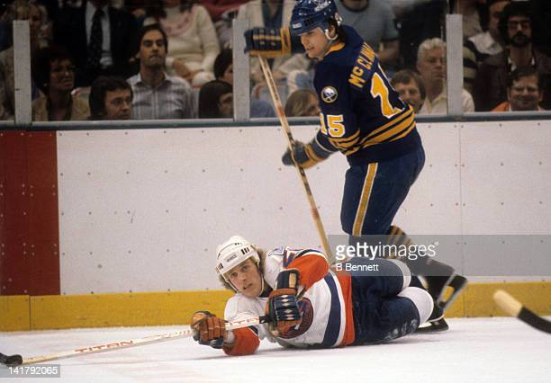 Mike Bossy of the New York Islanders reaches for the puck while on the ground as Rob McClanahan of the Buffalo Sabres skates by him circa 1981 at the...