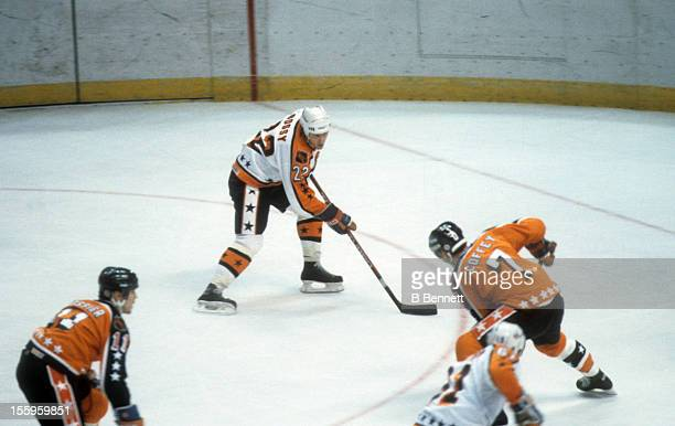 Mike Bossy of the Wales Conference and the New York Islanders skates with the puck as he is defended by Paul Coffey of the Campbell Conference and...