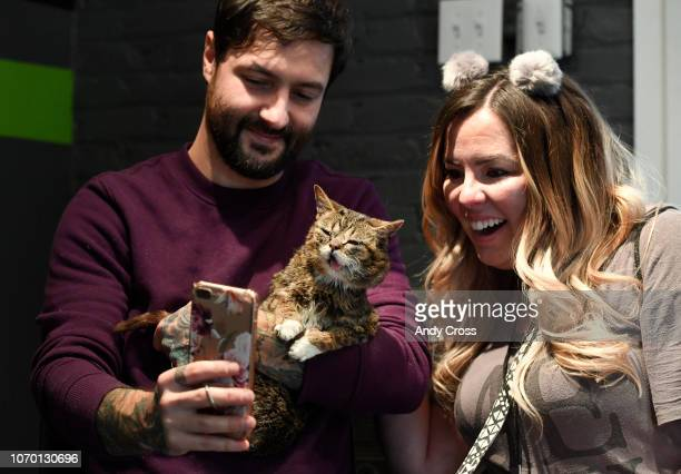 Mike Bridavsky holds his cat Lil Bub while taking a selfie picture with Lil Bub fan from Utah Natalie Baker at the 1st annual Snowcats Cat Convention...