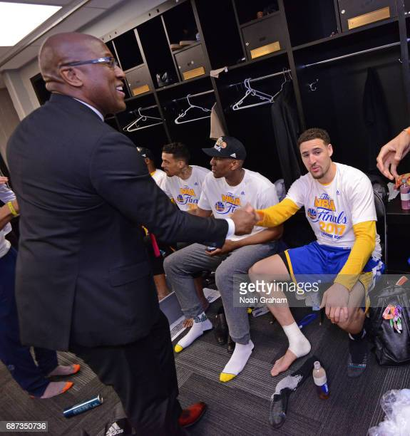 Mike Brown and Klay Thompson of the Golden State Warriors shake hands in the locker room after winning Game Four of the Western Conference Finals...