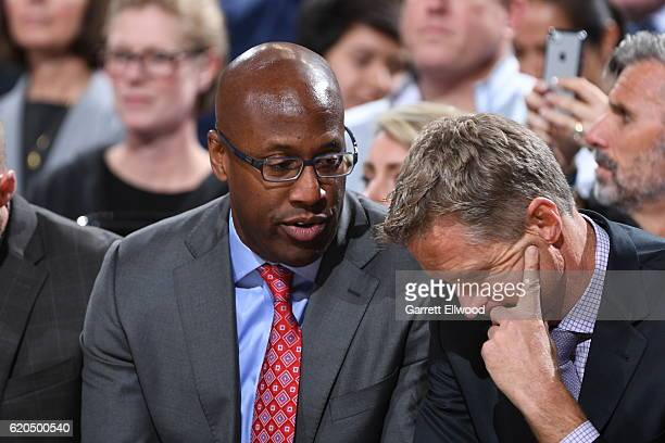 Mike Brown assistant coach of the Golden State Warriors talks with head coach Steve Kerr during the game against the Portland Trail Blazers on...