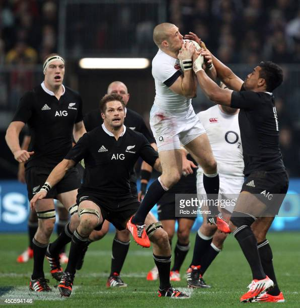 Mike Brown of England claims the high ball despite the attention of Julian Savea Richie McCawand Brodie Retallick of New Zealand during the...