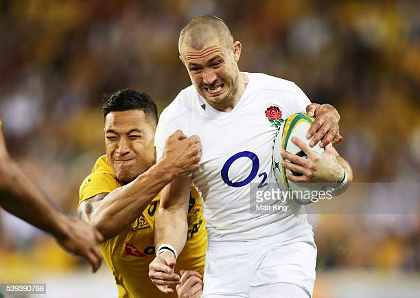 Mike Brown of England is tackled by Israel Folau of the Wallabies during the International Test match between the Australian Wallabies and England at...