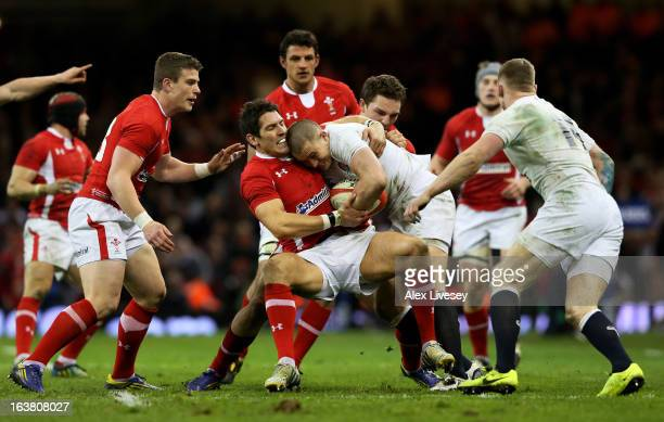 Mike Brown of England is wrapped up by James Hook of Wales during the RBS Six Nations match between Wales and England at Millennium Stadium on March...