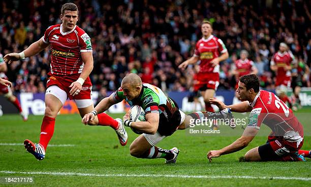 Mike Brown of Harlequins beats the tackle of Steven Shingler of Scarlets to score his team's first try of the game during the Heineken Cup match...