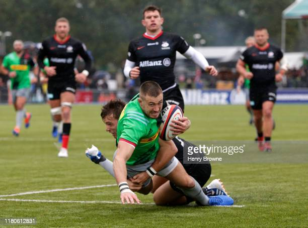 Mike Brown of Harlequins goes over to score his team's first try under a challenge from Alex Lewington of Saracens during the Premiership Rugby Cup...