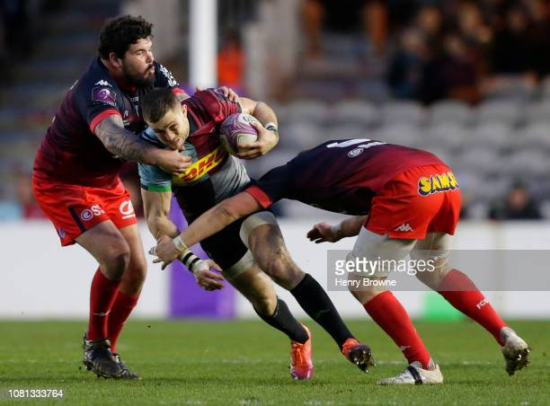 Mike Brown of Harlequins is tackled by Alexandre Dardet and Antonin Berruyer of Grenoble during the Challenge Cup match between Harlequins and...