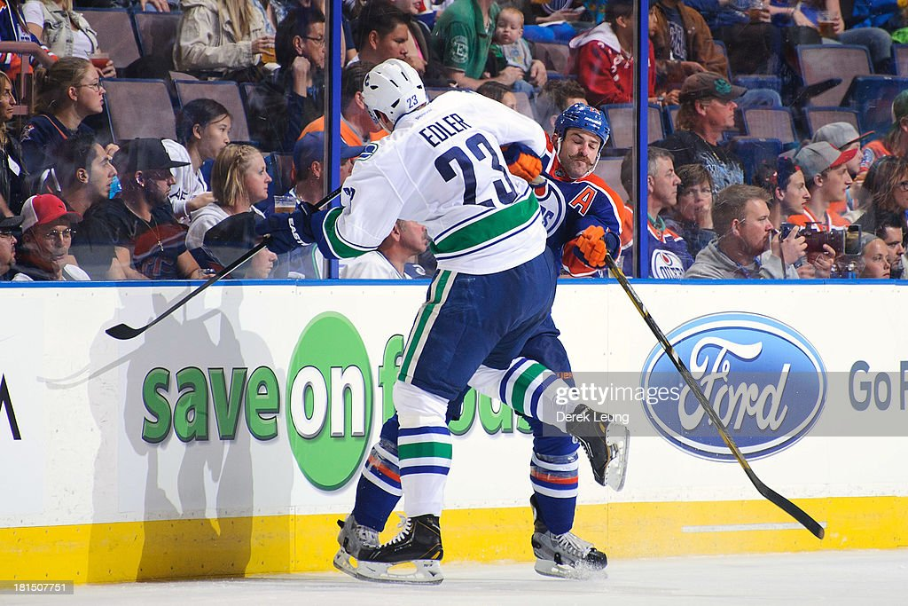 Mike Brown #13 of the Edmonton Oilers collides with Alexander Edler #23 of the Vancouver Canucks during a preseason NHL game at Rexall Place on September 21, 2013 in Edmonton, Alberta, Canada.