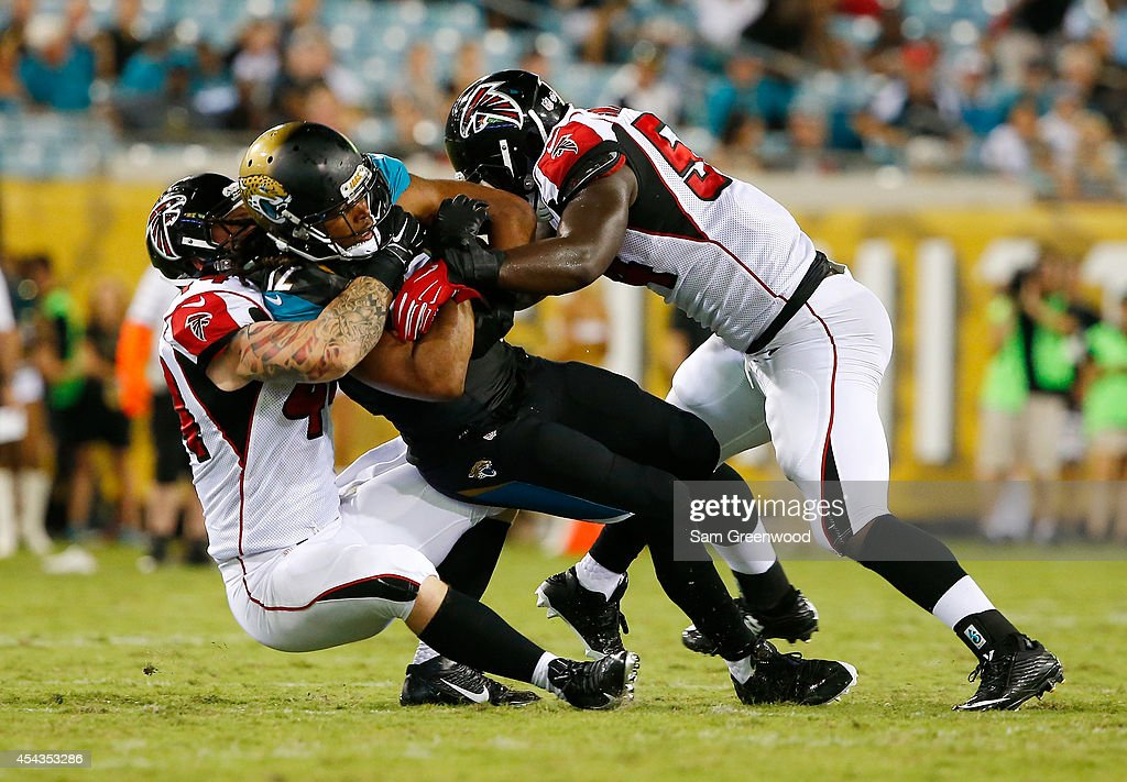 Mike Brown #12 of the Jacksonville Jaguars is tackled by Pat Angerer #44 of the Atlanta Falcons and Jonathan Massaquoi #94 during the preseason NFL game at EverBank Field on August 28, 2014 in Jacksonville, Florida.