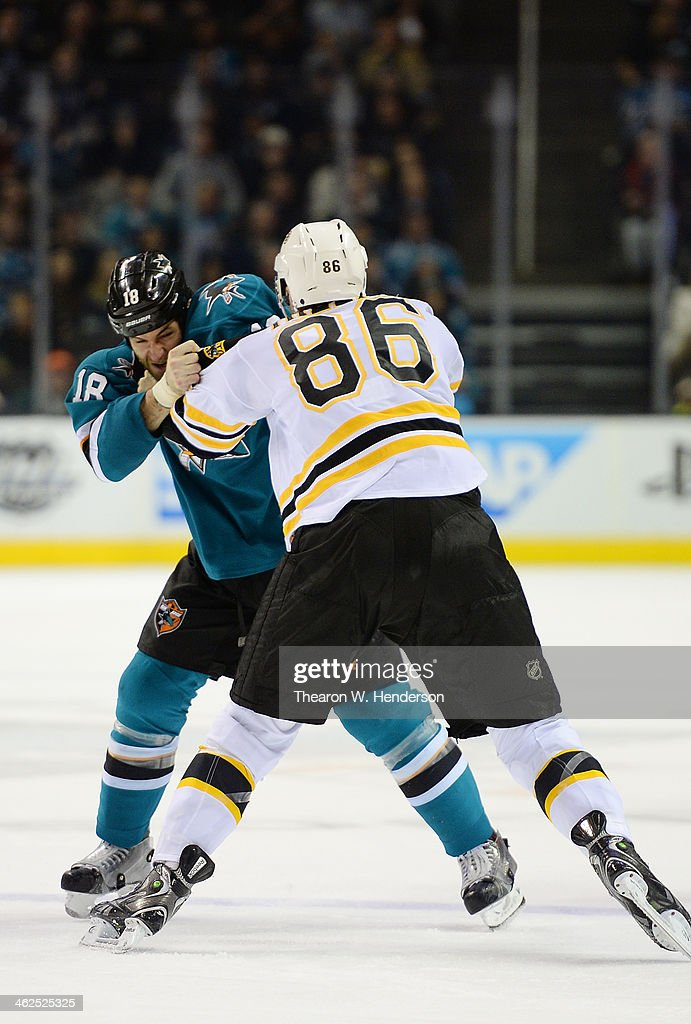 Mike Brown #18 of the San Jose Sharks and Kevan Miller #86 of the Boston Bruins exchange punches in a fight during the second period at SAP Center on January 11, 2014 in San Jose, California.