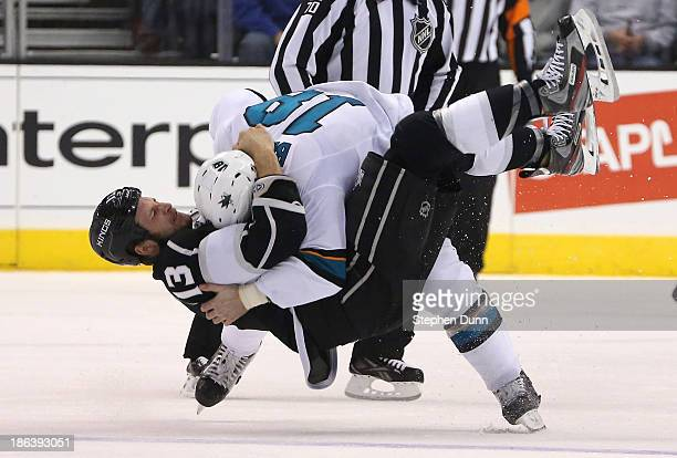 Mike Brown of the San Jose Sharks and Kyle Clifford of the Los Angeles Kings go the ice as they fight in the first period at Staples Center on...
