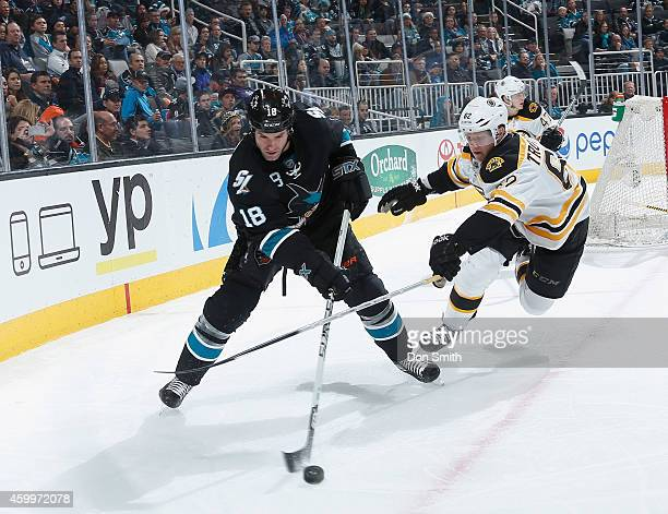Mike Brown of the San Jose Sharks aneles the puck against Zach Trotman of the Boston Bruins during an NHL game on December 4, 2014 at SAP Center in...
