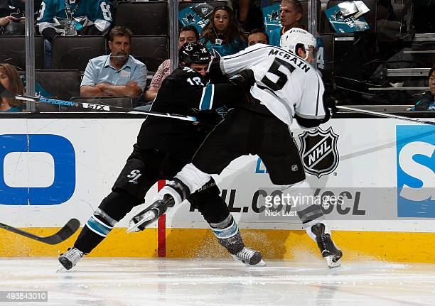 Mike Brown of the San Jose Sharks delivers a hit against Jamie McBain of the Los Angeles Kings during a NHL game at the SAP Center at San Jose on...